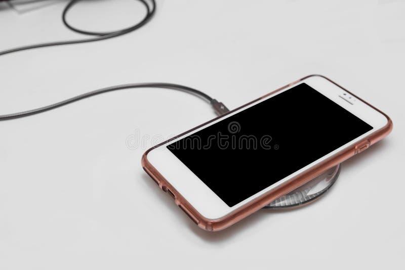 Mobiltelefon på det trådlösa laddande blocket arkivbilder