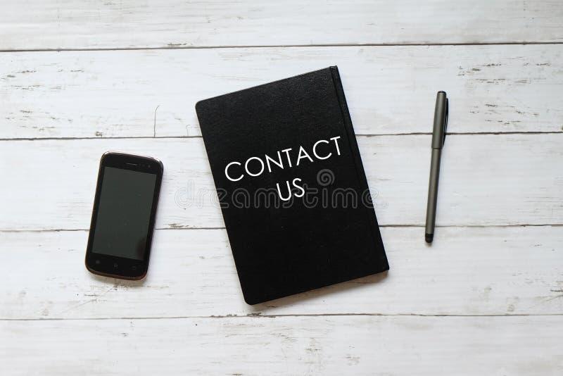 Mobiltelefon, penna och anteckningsbok för bästa sikt som är skriftliga med KONTAKTEN USA på vit träbakgrund arkivbilder
