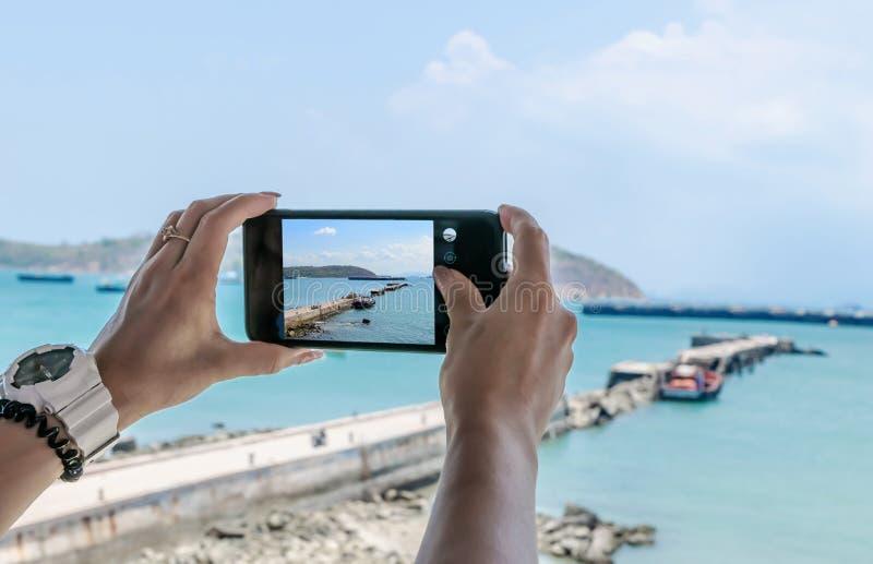 Mobiltelefon Smartphone och att ta bilder av havet och berget arkivfoton