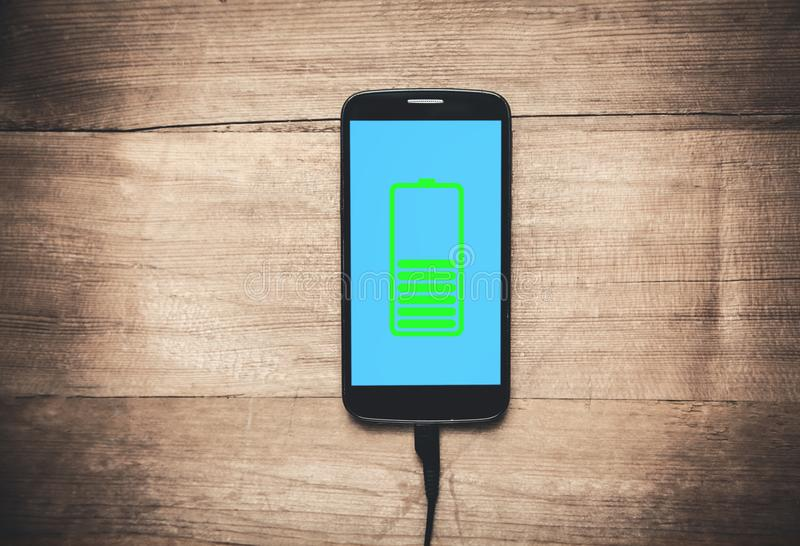 Mobiltelefon som laddar på träskrivbordet arkivfoto