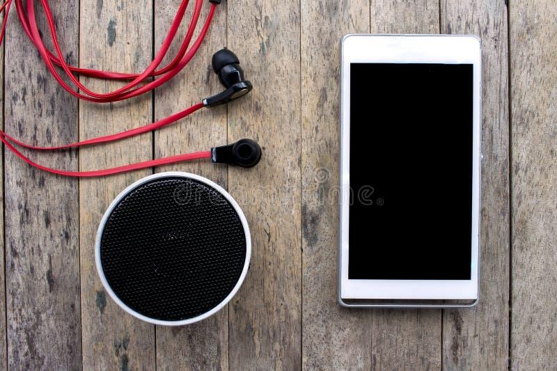 Mobiltelefon und bluetooth Sprecher und Kopfhörer auf hölzernem Hintergrund lizenzfreie stockfotos