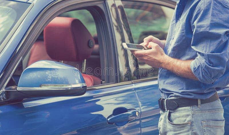 Mobiltelefonapps för bilägare Man som använder smartphonen för att kontrollera statuskontrollbilen royaltyfri fotografi