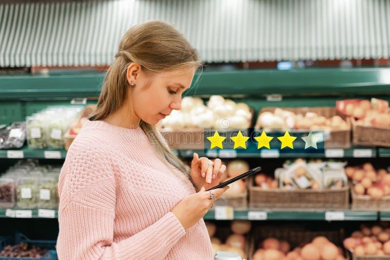 Mobiltelefone und soziale Netze Eine junge Frau steht in einem Lebensmittelgeschäft und liest Nachrichten auf ihrem Handy In lizenzfreie stockfotos