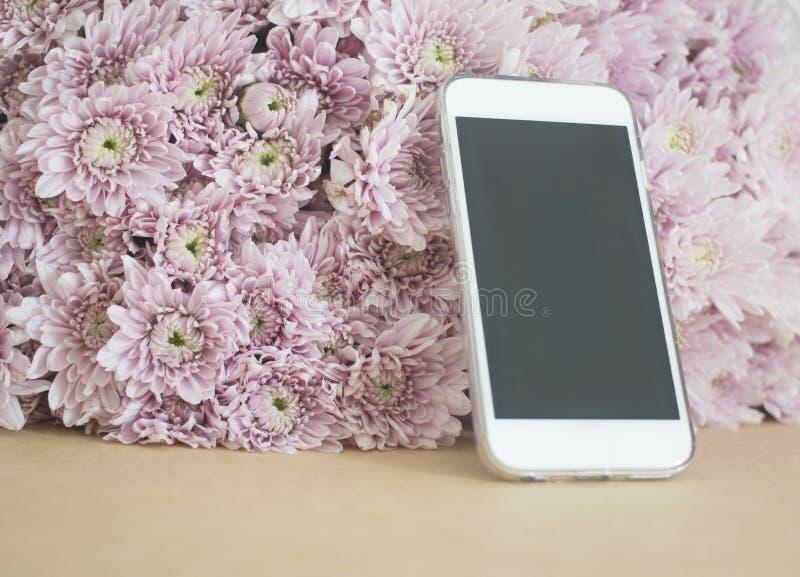 Mobiltelefonen med rosa färger blommar bakgrund arkivbilder
