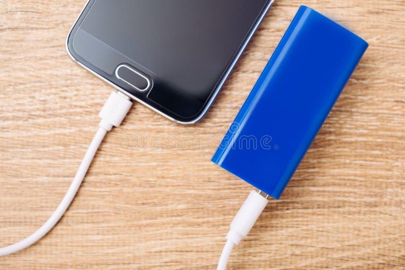 Mobiltelefonen och batteridrift packar ihop uppladdaren på ett kontorsskrivbord arkivbilder