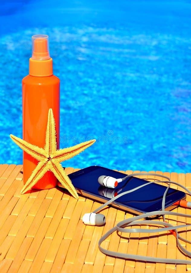 Mobiltelefonen, solsprej, huvudtelefoner och sjöstjärnan nära bevattnar royaltyfri fotografi