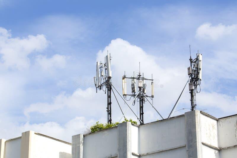 Mobiltelefonen står högt på invånarebyggnadstaket med blå himmel royaltyfria foton