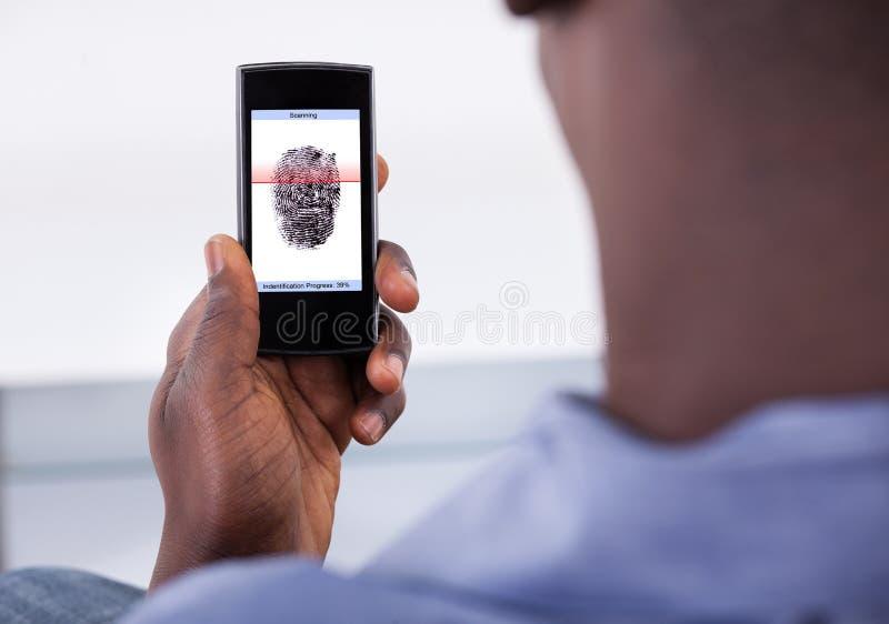 Mobiltelefonlegitimation genom att använda fingeravtryckbildläsning royaltyfria foton