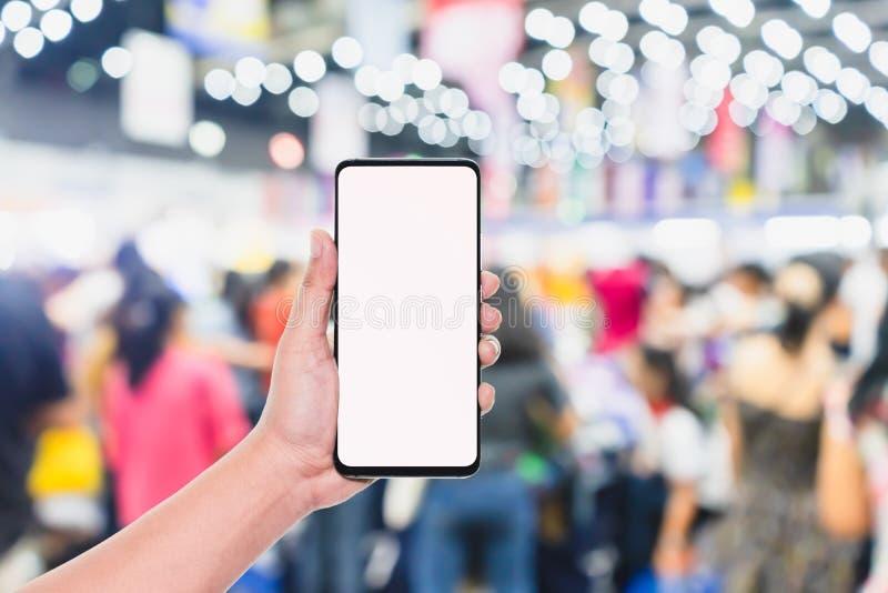 Mobiltelefonmodellbild, hand som rymmer den mobila smarta telefonen för tom skärm med den suddiga folkmassan av folk i det shoppa royaltyfria foton