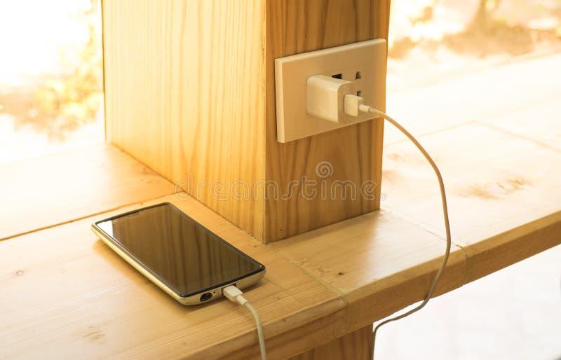 Mobiltelefonuppladdare som pluggas på träpol royaltyfri foto