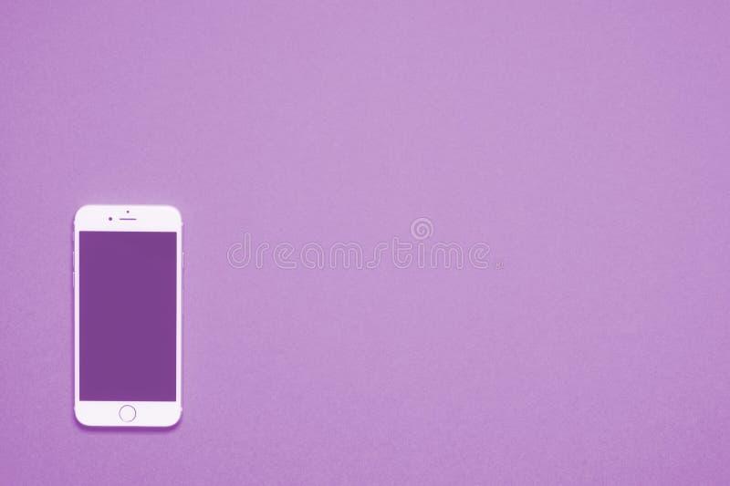 Mobiltelefonvit mot vanligt purpurfärgat bakgrundskort fotografering för bildbyråer
