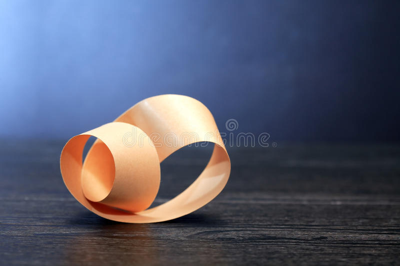 Mobius Strip On Dark. Paper Mobius strip on wooden board against dark background stock photography