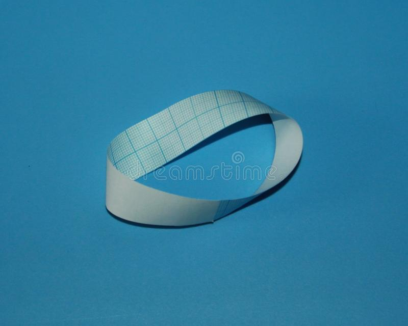 Mobius strip paper ring lies on a table.  royalty free stock photography
