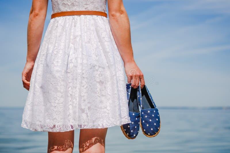 Mocassini della tenuta della donna sulla spiaggia che cammina in vestito bianco fotografie stock