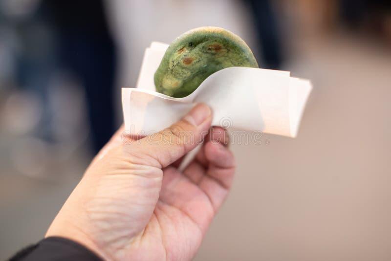 Mochi grüner Tee des Handholdingbrandes, ein japanischer Nachtisch lizenzfreie stockfotografie