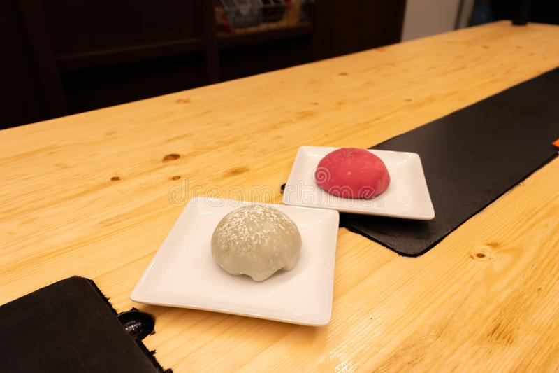 Mochi grande do chá verde e da framboesa vermelha em uma placa em uma tabela de madeira em um restaurante asiático ou em umas bol imagens de stock