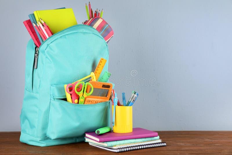 Mochila brillante con efectos de escritorio de la escuela en la tabla de madera marrón contra fondo gris foto de archivo