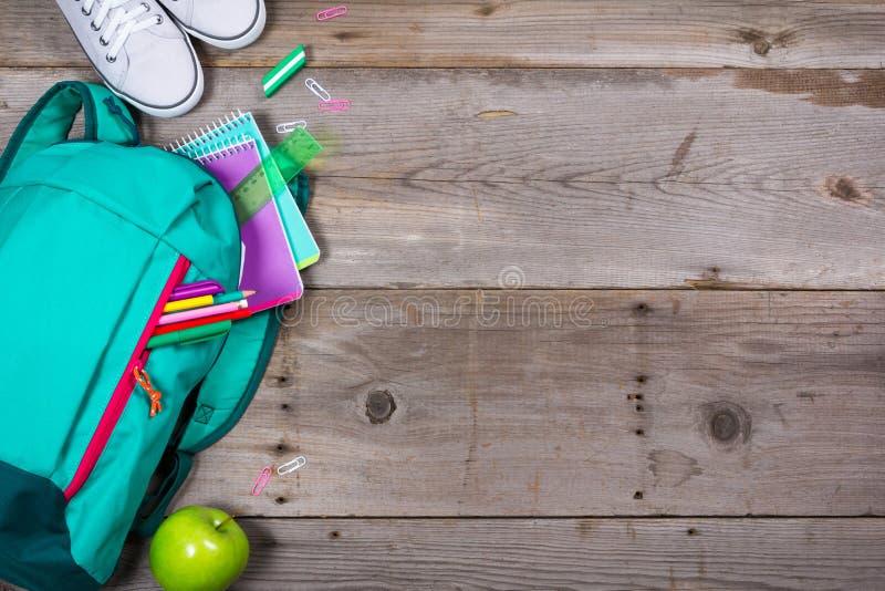 Mochila con efectos de escritorio de la escuela en fondo de madera foto de archivo libre de regalías
