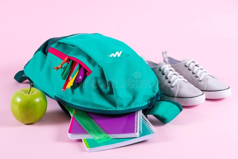 Mochila con efectos de escritorio de la escuela en fondo rosado imagen de archivo