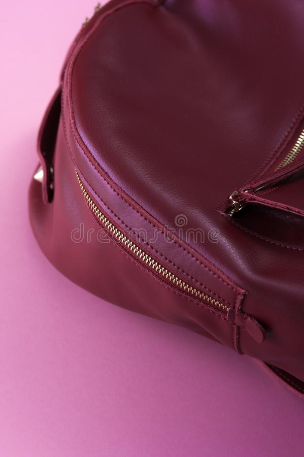 Mochila de cuero roja en fondo rosado imagen de archivo libre de regalías