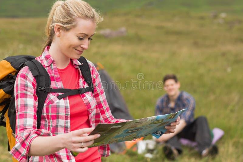 Mochila de la mujer feliz y mapa el sostenerse que llevan fotos de archivo