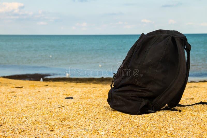 Mochila del viaje en la playa arenosa del mar del verano foto de archivo