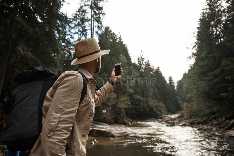 Mochila del viajero joven y fotos el tomar que llevan de la naturaleza imagenes de archivo