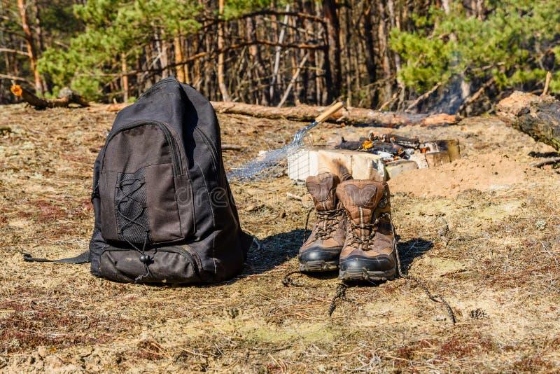 Mochila e botas turísticas num terreno em uma floresta de coníferas, Bonfire, num fundo fotos de stock