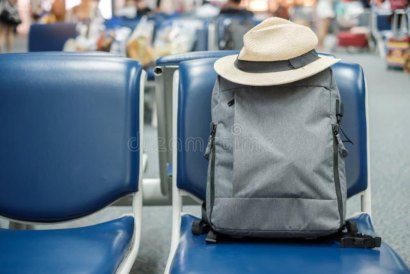 Mochila gris del negocio con el sombrero en asiento en el interior del terminal de aeropuerto Concepto del negocio y del viaje fotografía de archivo