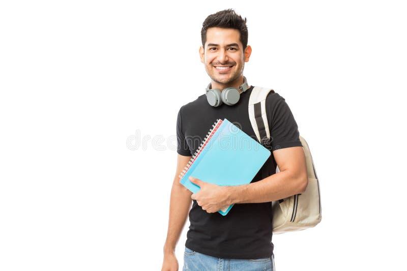 Mochila joven sonriente de With Books And del estudiante universitario fotos de archivo