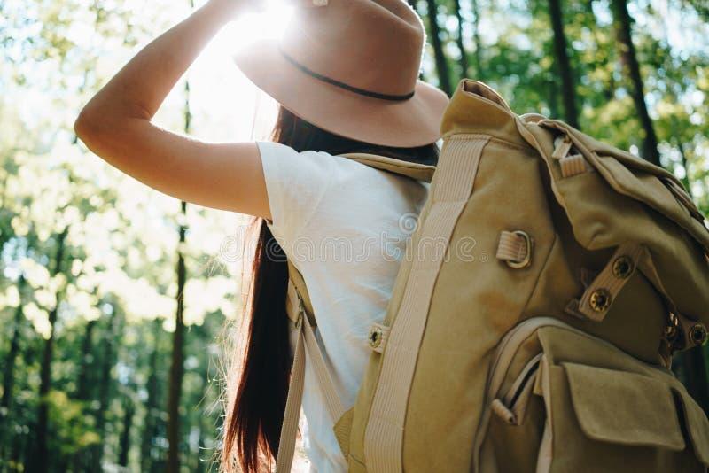 Mochila que lleva y sombrero de la mujer valiente del inconformista que viajan solamente entre árboles en bosque encendido al air fotos de archivo libres de regalías