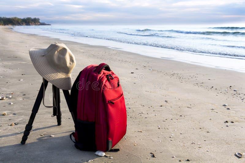 Mochila roja turística del inconformista con la cámara del sombrero y del trípode en la playa imagen de archivo libre de regalías