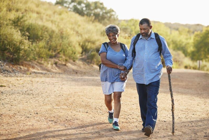 Mochilas que llevan de los pares mayores que caminan en campo junto imagen de archivo libre de regalías