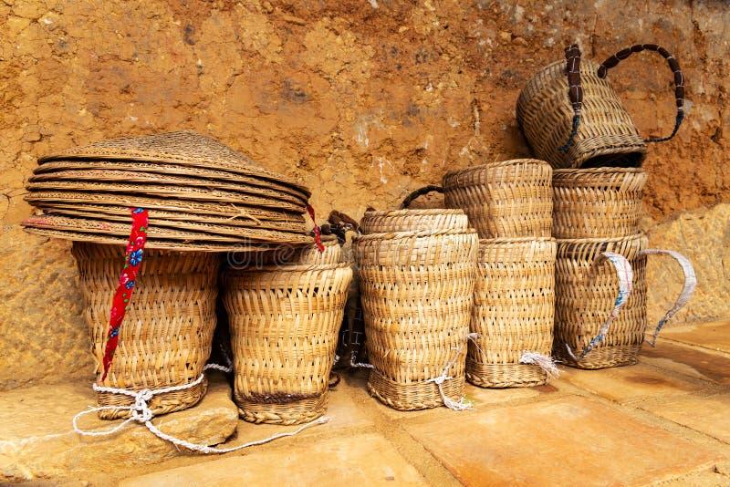 Mochilas tradicionales de la cesta de Hmong y una pila de sombreros vietnamitas tradicionales por una pared de una casa del hmong imágenes de archivo libres de regalías