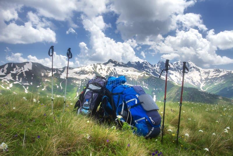 Mochilas y bastones de la montaña en pista de senderismo El caminar en concepto de las montañas Turismo del deporte fotos de archivo
