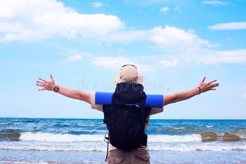 Mochileiro com as mãos espalhadas que expressam a felicidade no bea do mar imagens de stock royalty free