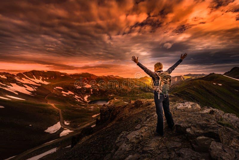 Mochileiro da jovem mulher em Victory Pose com os braços sobre acima aumentados a imagens de stock