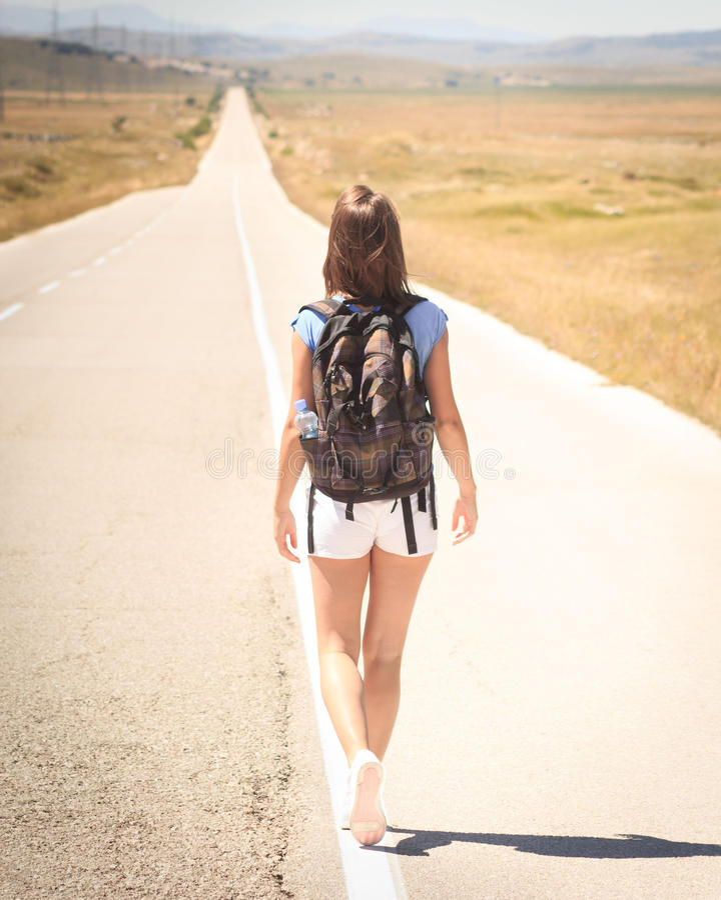 Mochileiro da mulher que anda na estrada fotografia de stock