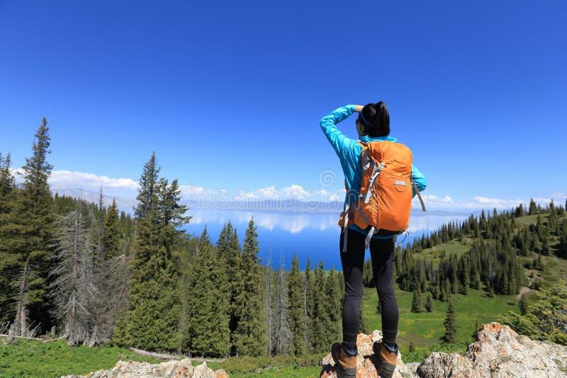 Mochileiro da mulher que caminha na fuga de montanha da floresta imagem de stock
