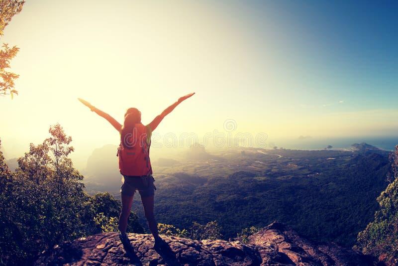 Mochileiro da mulher que caminha no penhasco do pico de montanha do nascer do sol imagens de stock royalty free