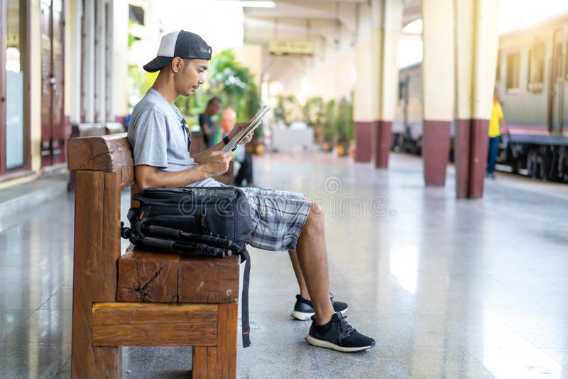 Mochileiro de viagem do homem asiático com leitura do mapa no estação de caminhos de ferro foto de stock royalty free