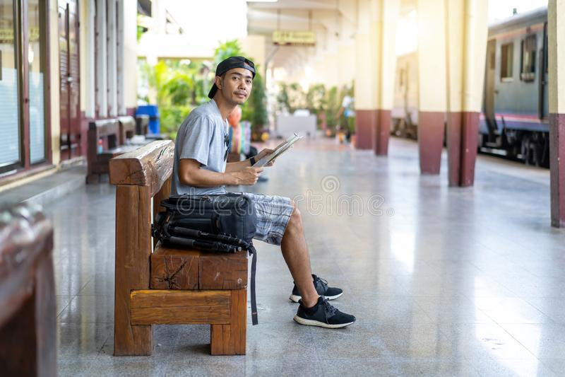 Mochileiro de viagem do homem asiático com leitura do mapa no estação de caminhos de ferro fotos de stock royalty free