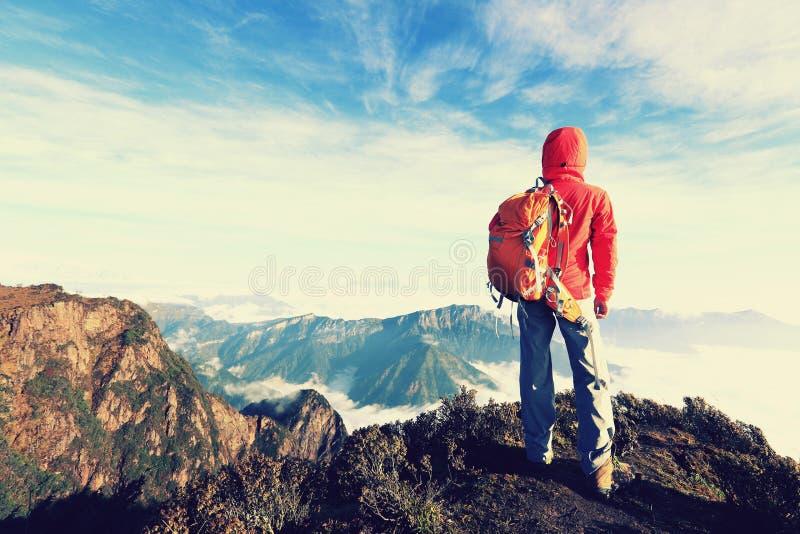 mochileiro determinado da mulher que caminha no pico de montanha imagens de stock royalty free