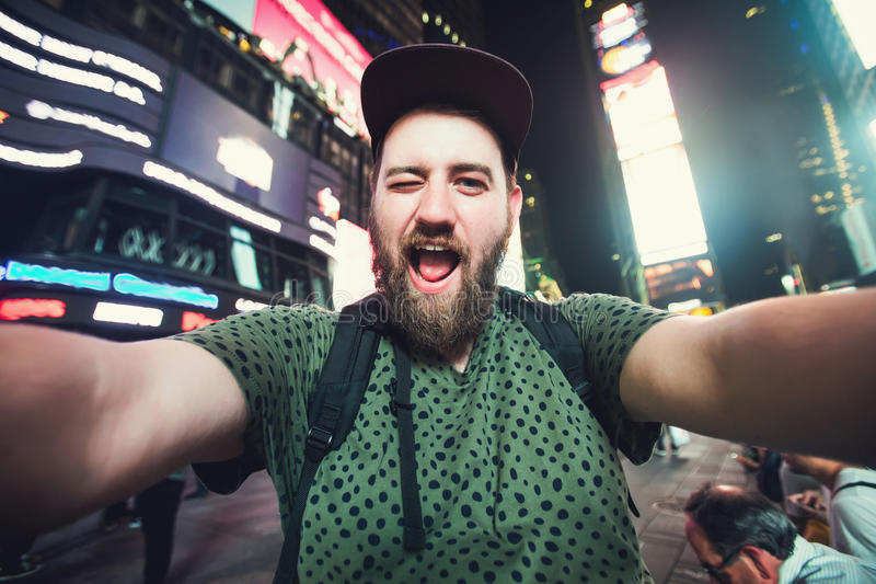 Mochileiro farpado engraçado do homem que sorri e que toma a foto do selfie no Times Square em New York quando curso através dos  imagens de stock royalty free