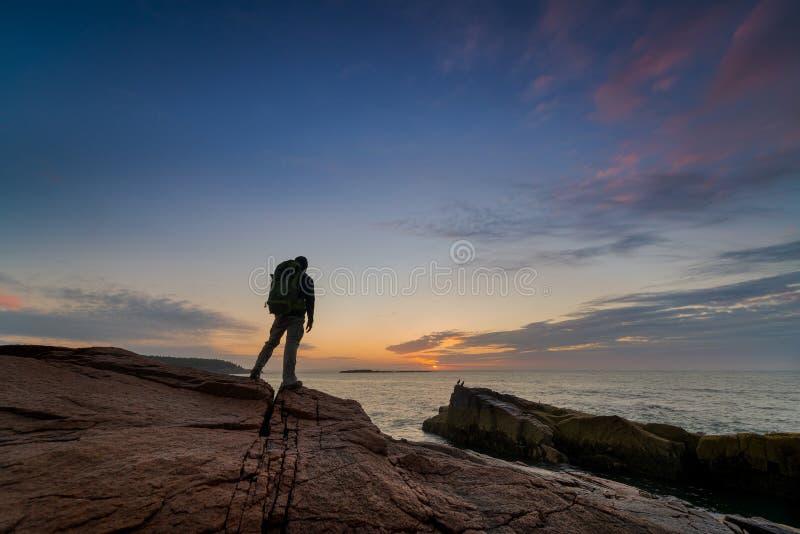 Mochileiro que olha um nascer do sol no parque nacional do Acadia foto de stock