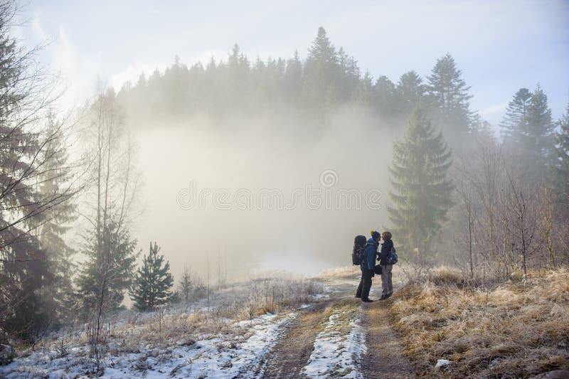 Mochileiros do homem e da mulher que apreciam na fuga de montanha nevoenta da floresta imagens de stock