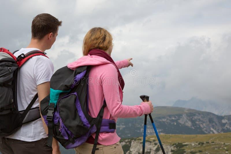 Mochileiros novos que procuram o destino nas montanhas fotos de stock royalty free