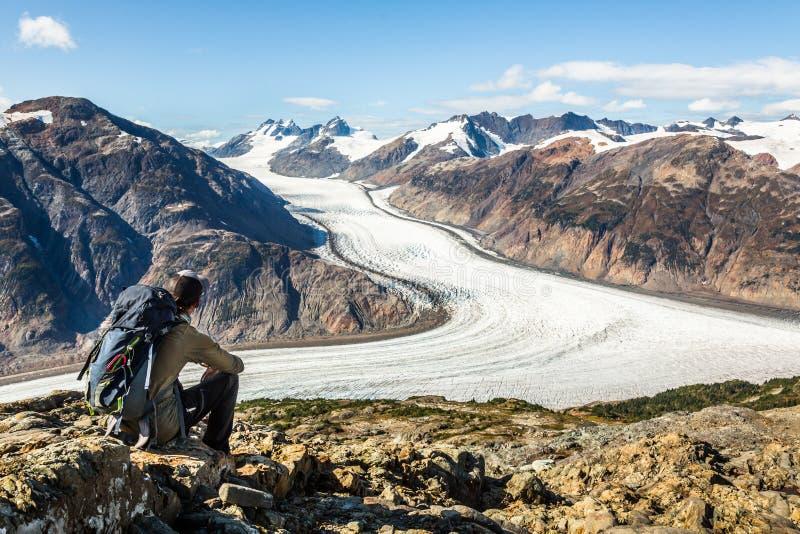 Mochilero descansando en una roca sobre el glaciar Salmon en las montañas canadienses cerca de Alaska fotografía de archivo libre de regalías