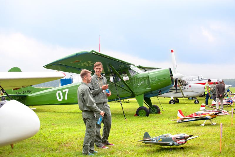 Mochishche airfield, local air show, biplane yak 12 M and two smiling young men in pilot clothes on vintage airplane background royalty free stock photo