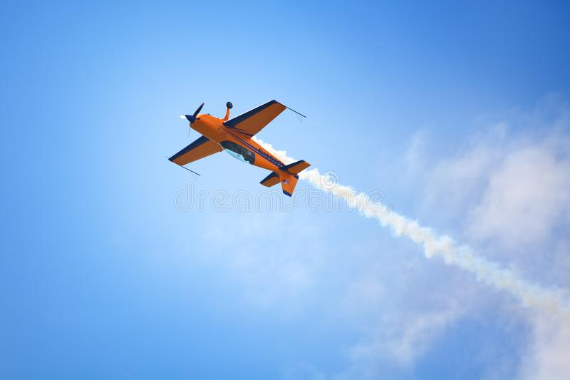 Mochishche airfield, local air show, yellow Extra EX 360 sports plane upside down on blue sky and white clouds background, closeup royalty free stock photos
